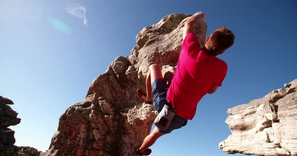 Low angle of strong rock climbing man hanging free on rock with sunflare against blue sky. Royalty-free stock video