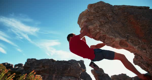 Confident rock climber conquering the challenge of bouldering on a sunny day. He is fit, strong and focused on the ascent of the mountain. Royalty-free stock video