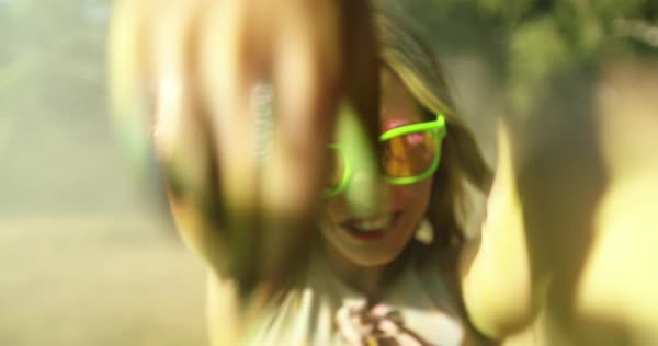 Close-up face shot of Holi powder covered young woman smiling and making peace sign in a park Royalty-free stock video