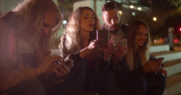 Teenager hipster friends spending time with smarphones sitting on the steps of a monument on evening Royalty-free stock video