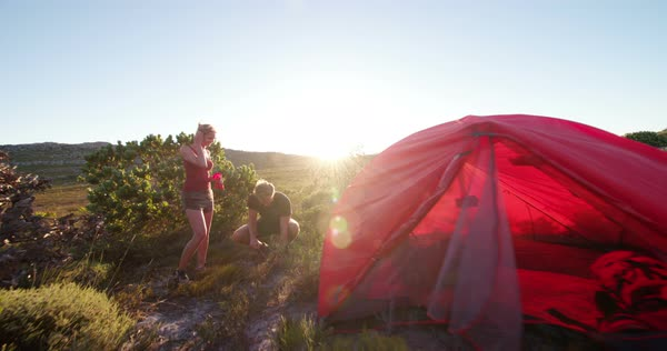 Hiker setting up tent while woman hands him a tent peg. The hiking couple is camping in the wilderness at sunset on their outdoor hiking adventure vacation. Royalty-free stock video