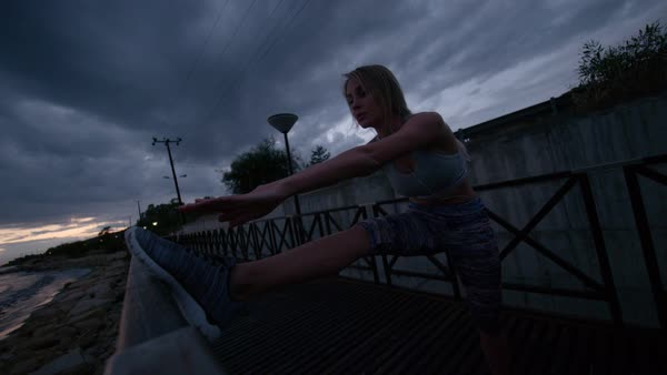 Beautiful young blond woman stretching her legs during early morning workout. Royalty-free stock video