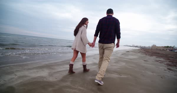 Beautiful young couple on a date walking on the beach, holding hands and casually talking Royalty-free stock video