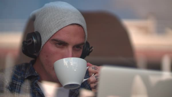 Young man drinking coffee, listening to music and watching his laptop screen by cafe window Royalty-free stock video