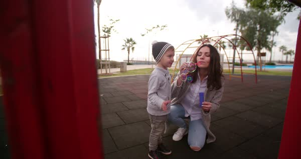 Cute boy poppping bubbles his mum blew for him to play with at the park Royalty-free stock video