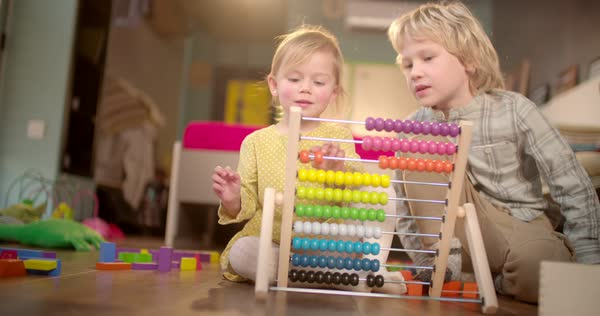 Little sister learning how to count on abacus with the help of her older brother Royalty-free stock video