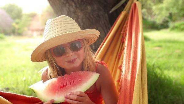 Happy girl in hammock holding fresh watermelon slice Royalty-free stock video