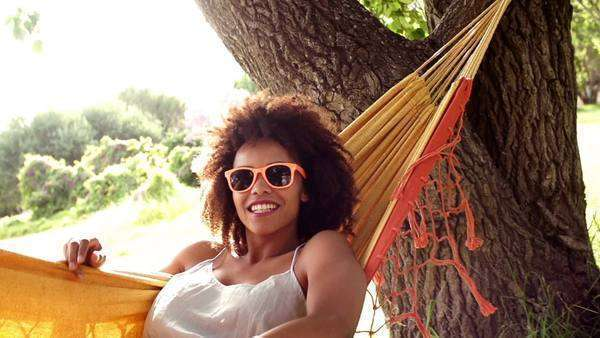 Young African American woman relaxing in a hammock at park in slow motion Royalty-free stock video