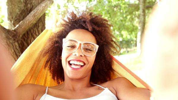 Young African American woman lying in hammock laughing in slow motion Royalty-free stock video