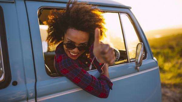 Woman in vintage car laughing at sunset doing thumbs up Royalty-free stock video