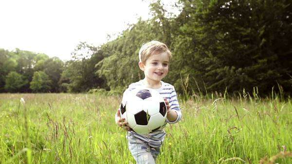 Little boy running through tall grass with soccer ball Royalty-free stock video