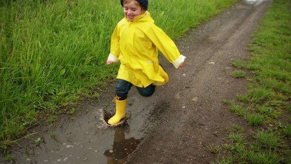 Young boy running through puddle after rain in slow motion Royalty-free stock video