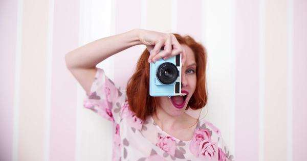 Young redhead woman laughing taking pictures with vintage camera in her hand Royalty-free stock video