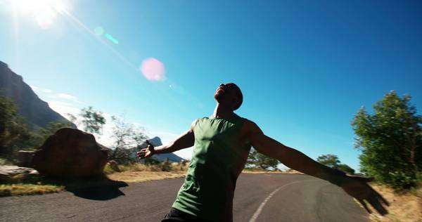 Man running with his arms outstretched down a mountain road in slow motion Royalty-free stock video