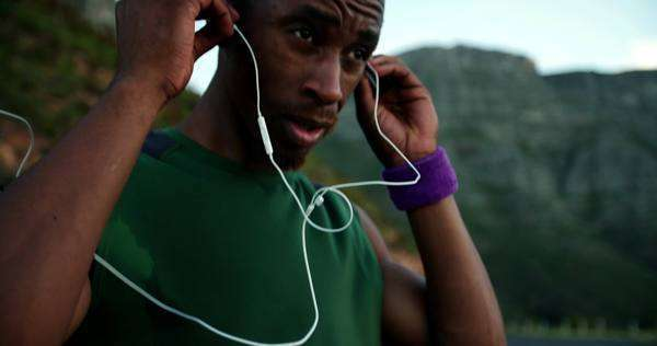 Runner putting his earphones in before his starts his fitness training in slow motion Royalty-free stock video