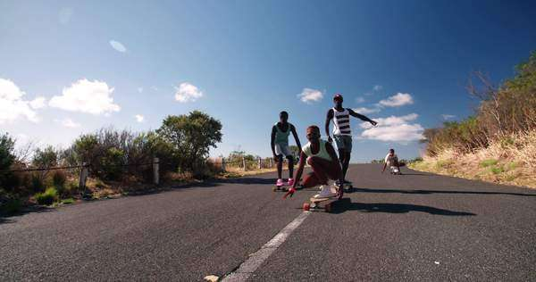 Mixed group of teenaged skateboarders racing each other downhill on a deserted road in slow motion Royalty-free stock video