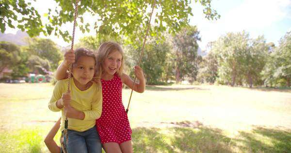Childhood friends on a swing together happily in a park surrounded by nature, slow motion Royalty-free stock video