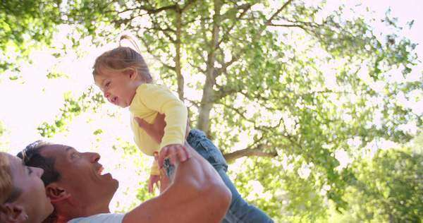 Parents laughing while playing with their happy little girl in a sunlit park, in slow motion Royalty-free stock video