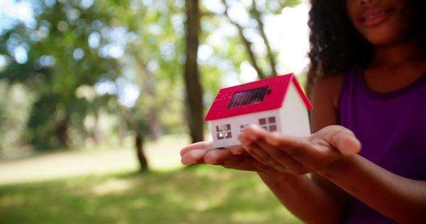 Close-up of a toy house with a solar cell on it's roof being held by girl who is blurred in the background Royalty-free stock video
