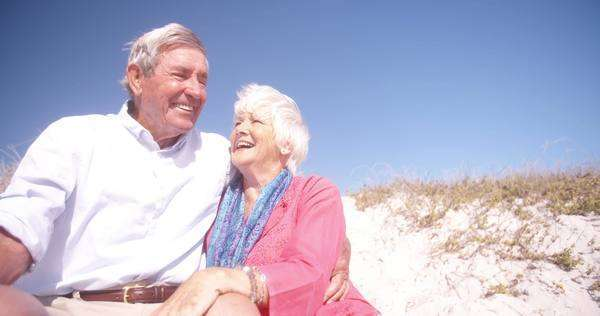 Laughing retired senior couple sitting happily on a sand dune at the beach together in slow motion Royalty-free stock video