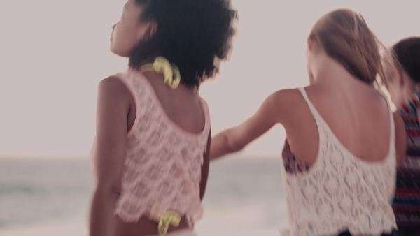 Rear view of an girl holding hands with her friends having fun on the beach together at dusk Royalty-free stock video