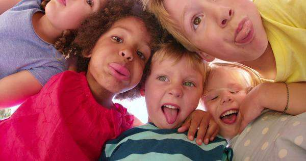 Mixed racial group of kids posing happily above the camera and smiling playfully in slow motion Royalty-free stock video