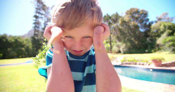 Cute little boy laughing and posing playfully holding up carrots as ears Royalty-free stock video
