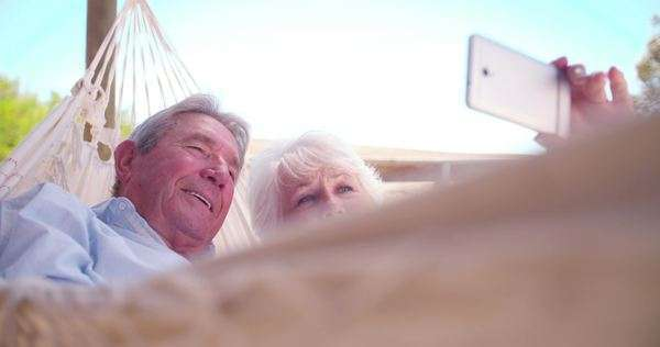 Smiling retired senior couple lying down together in hammock and taking a selfie with their smart phone in slow motion Royalty-free stock video
