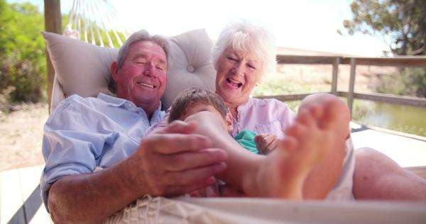 Retired grandparents with their grandson on their laps laughing while tickling him in slow motion Royalty-free stock video