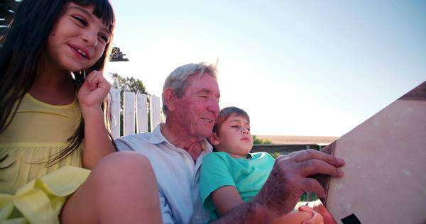 Happy grandpa reading a story to his little grandkids outdoors Royalty-free stock video
