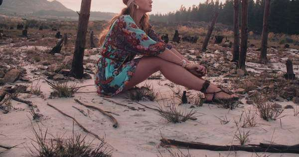 Full body shot of a boho girl in a floral dress sitting in a natural landscape in slow motion Royalty-free stock video