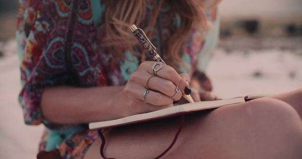 Cropped shot of a boho girl wearing a floral dress writing in her diary Royalty-free stock video