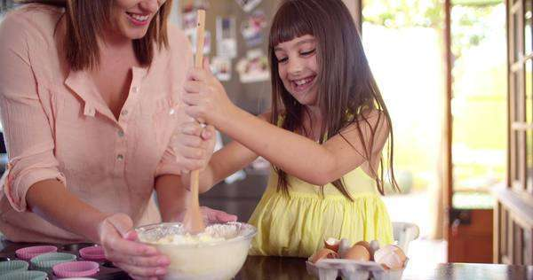 Little girl helping her mom in the kitchen by stirring the ingredients for their cake with a wooden spoon Royalty-free stock video