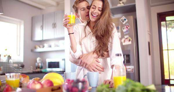 Happy couple in their kitchen for a healthy breakfast in the early morning in slow motion Royalty-free stock video