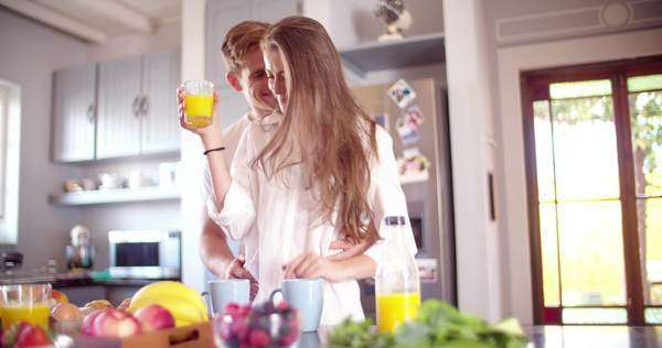 Loving guy hugging his smiling girlfriend in their kitchen early in the morning with breakfast being made in slow motion Royalty-free stock video