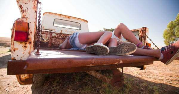 Low angle shot of the legs of a teen couple lying down and kissing in the open back of a vintage truck on a summer day Royalty-free stock video