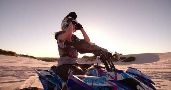 Female quad bike racer looking intently into the distance thinking about her competition with sun flare behind her, taking off helmet Royalty-free stock video