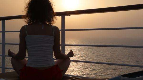 woman sits in pose of lotus on deckchair on deck of cruise ship in evening sea Royalty-free stock video