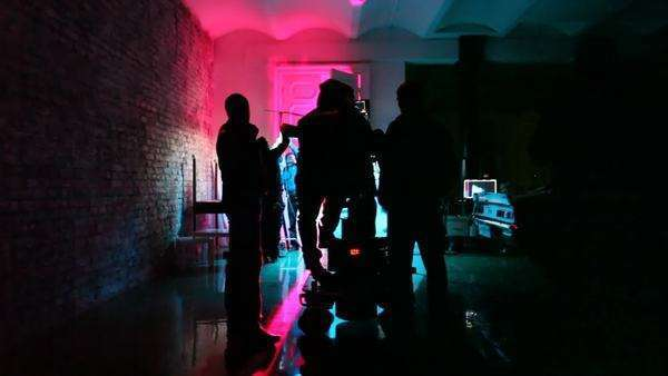 operator with videocamera and film crew in almost dark room prepare scenery Royalty-free stock video