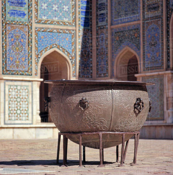 Afghanistan, Herat. An ancient brass cauldron rests in the inner courtyard at the colorful Friday Mosque, or Masjid-i-Jami, in Herat in Afghanistan. Royalty-free stock photo