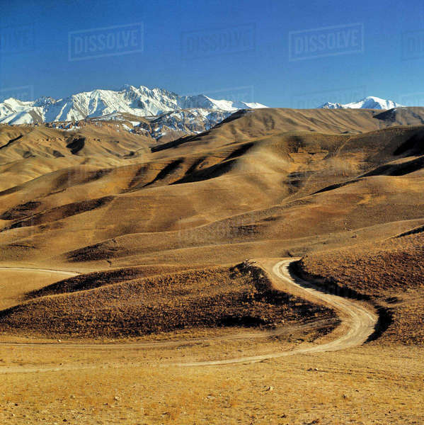 Afghanistan, Hindu Kush Mountains. A lonely dirt road leads into the barren foothills of the Hindu Kush Mountains in Afghanistan. Royalty-free stock photo