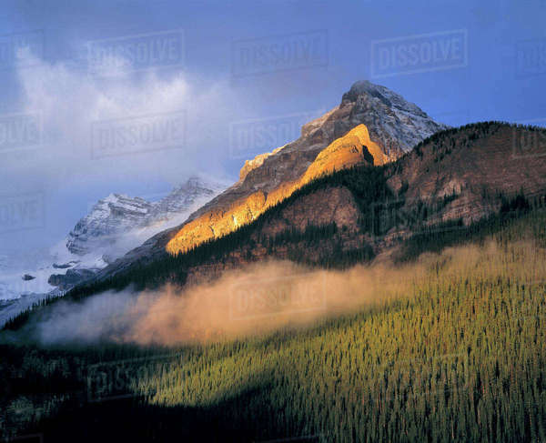 Canada, Alberta, Banff National Park. Sunrise strikes the flank of the Canadian Rockies as clouds swirl in Banff National Park, a World Heritage Site, Alberta, Canada. Royalty-free stock photo