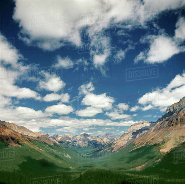 Canada, British Columbia, Yoho National Park. Puffy clouds shadow the green floor of a mountain valley, in Yoho National Park, a World Heritage Site, British Columbia, Canada. Royalty-free stock photo
