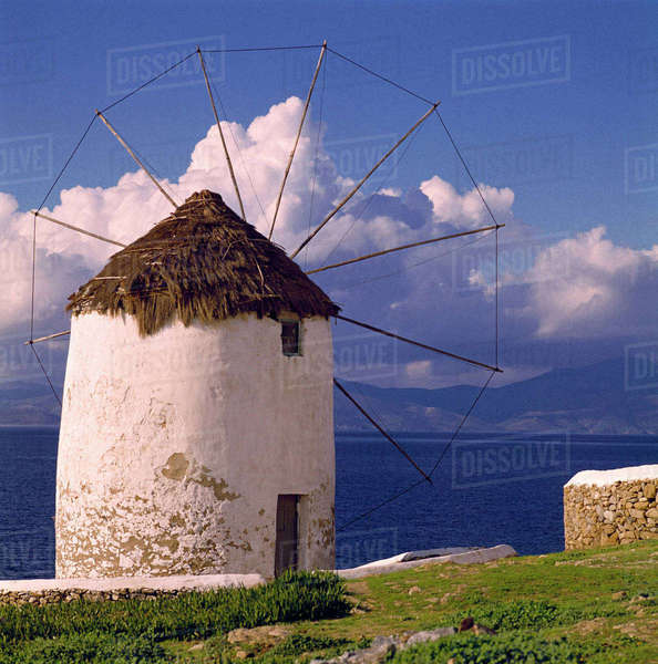 Europe, Greece, Mykonos. A striking white windmill looks over the azure sea in Mykonos, Greece. Rights-managed stock photo