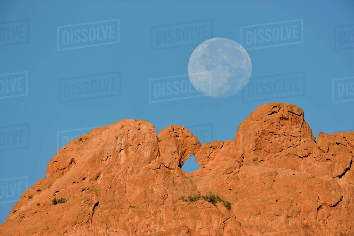 USA, Colorado, Colorado Springs, Garden of the Gods. A full moon sets  behind the Kissing Camels sandstone formation. stock photo