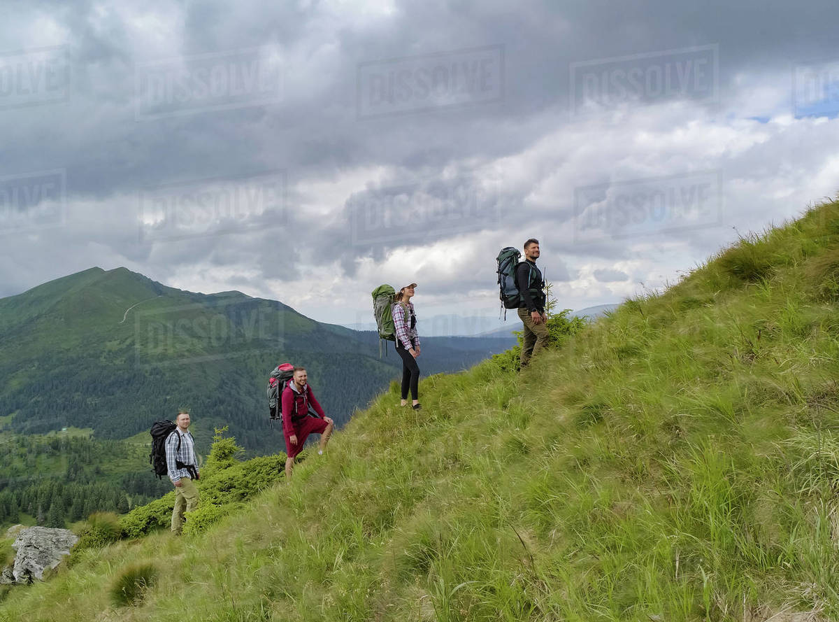 The four people with backpacks walking on the mountain Royalty-free stock photo
