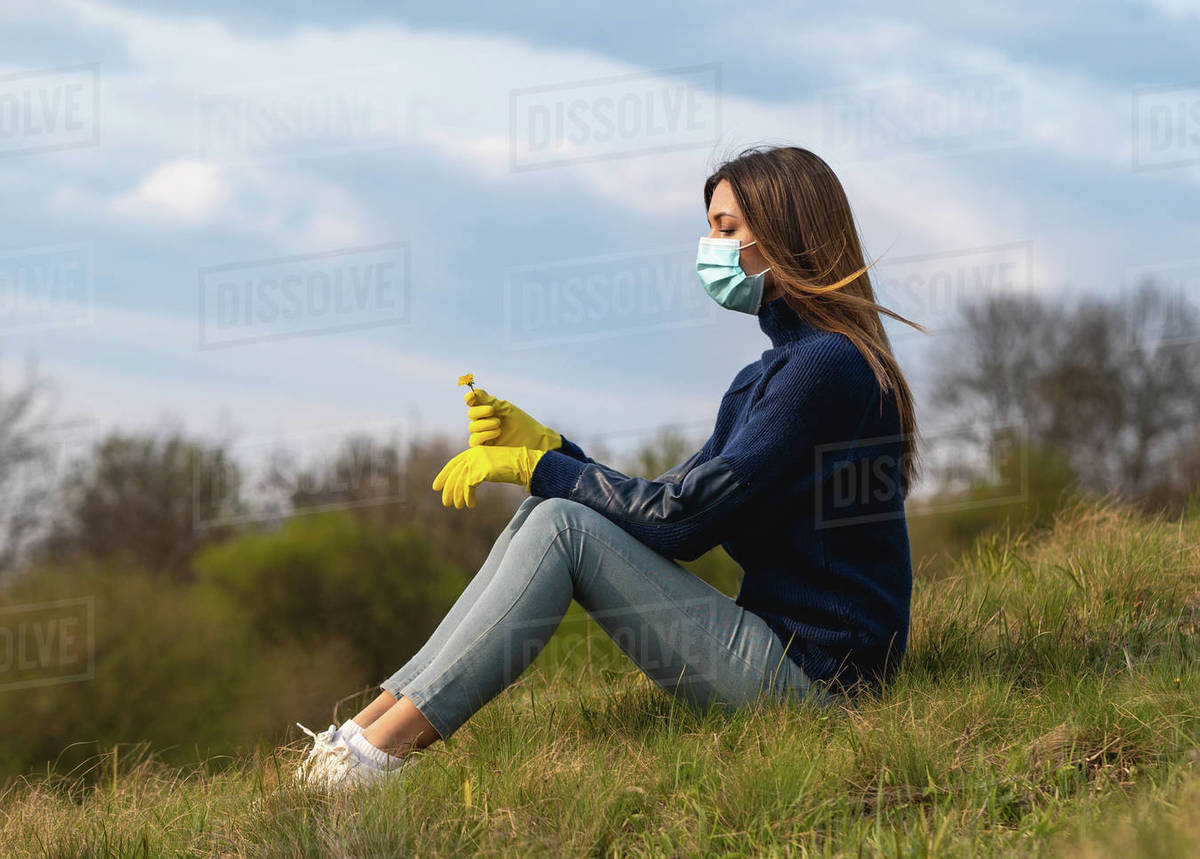 The young woman in medical mask and gloves sitting on the green grass Royalty-free stock photo
