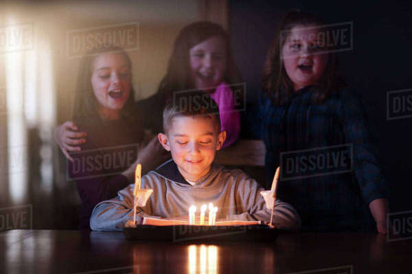 Boy surrounded by friends looking at birthday cake smiling Royalty-free stock photo