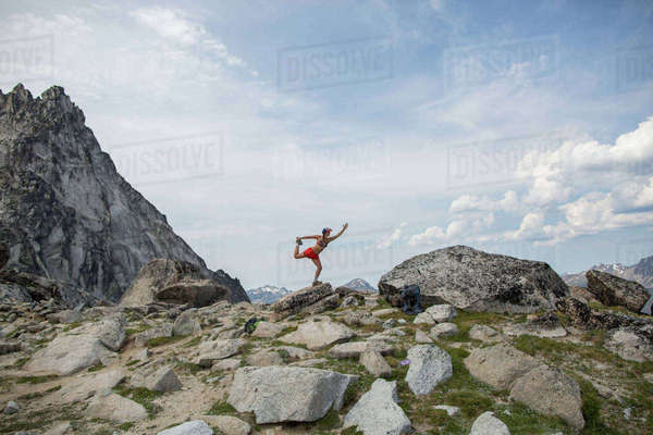 Young woman standing on rock, in yoga pose, The Enchantments, Alpine Lakes Wilderness, Washington, USA Royalty-free stock photo