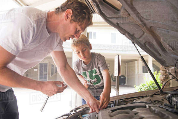 Father showing son car maintenance under car hood Royalty-free stock photo